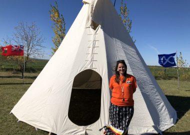 Stacey Desjardins, habillée en chandail orange et jupe noire, est debout devant un tipi blanc, le tout devant un grand ciel bleu des prairies.