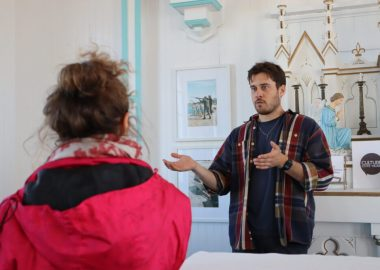 Un jeune artiste photographe gesticule avec ses mains, en expliquant à une spectatrice, vêtue de rouge aperçue de dos, des détails de son art. (Photo: Roger Clavet)