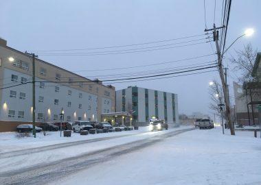 Une rue enneigée entre les édifices, sous un ciel gris