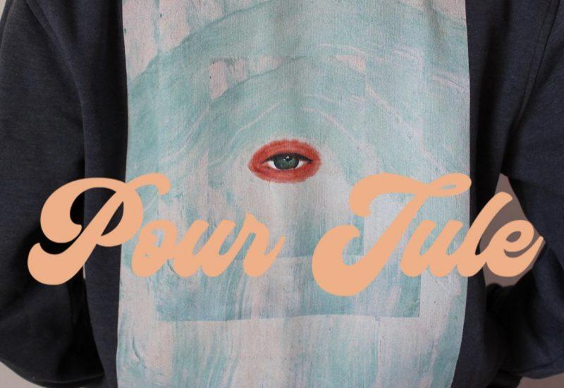 Une peinture bleue avec un oeil rouge sur un pull noir avec les mots «Pour Jule»