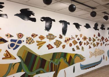 White wall with artwork of ten geese flying on the top, with artwork of pieces inside shapes of animals to be seen under the Tawatina bridge in November.