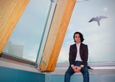 Mark Dhillon sits in front of a window at UNBC.