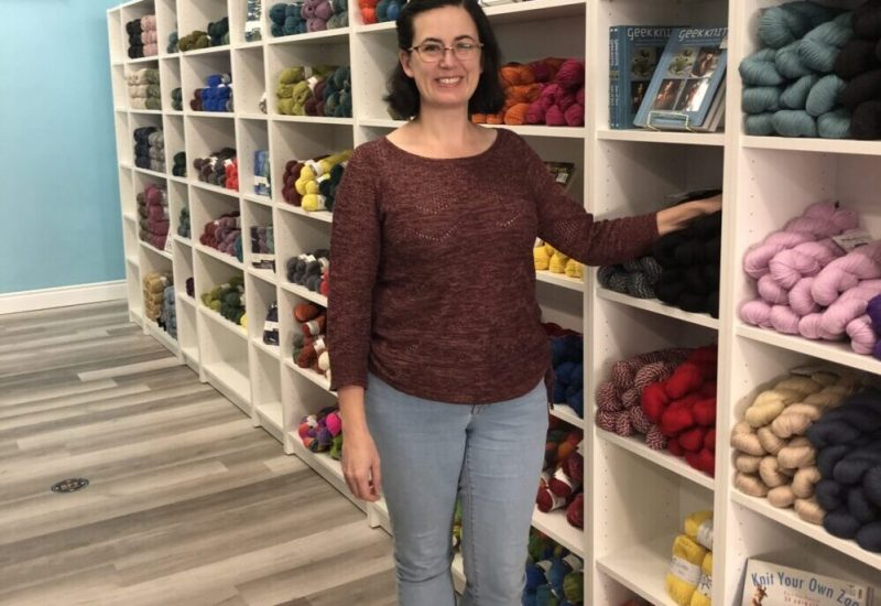 Miranda Holmes, owner & operator of String Theory Yarn, stands in front of a yarn display in her shop.