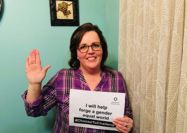 Helena Burke holding a sign about International Women's Day and holding a hand up to pledge