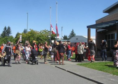 A crowd of Indigenous people, some with drums, heading for the front door of a police station