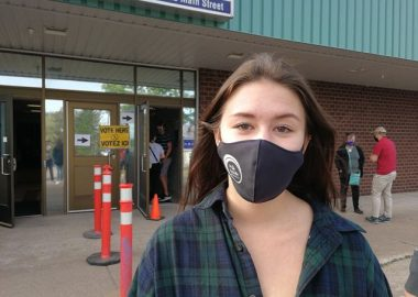 A photo of Sydney Thorburn outside a polling station at Mount Allison.