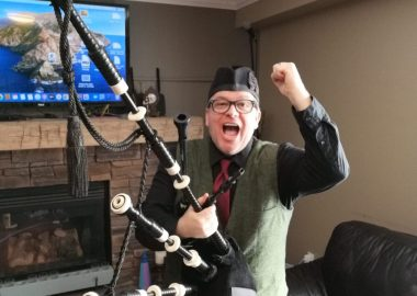 Peter Hummel holds his left fist in the air while holding bagpipes in his right hand and standing in a living room with a television on in the background