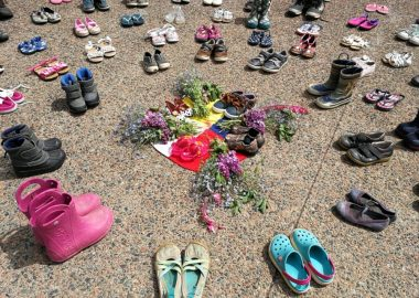 Childrens' shoes and flowers are arranged in a circle on pavement.