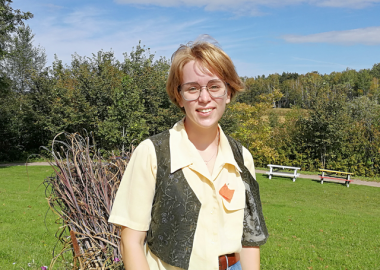 A young woman standing with a park in the background.