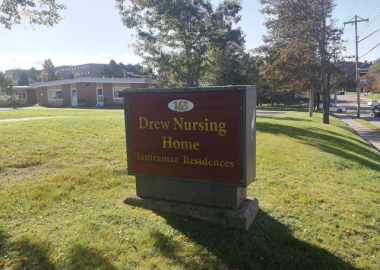 A sign with red background and gold lettering saying Drew Nursing Home, on a green lawn.