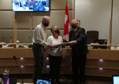 An older couple receive a gift from a man in a suit, all wearing COVID masks.