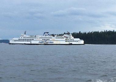 La mer au premier plan puis plus au large, un traversier blanc avec «BC Ferries» indiqué en bleu, des arbres en arrière-plan