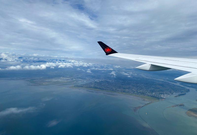Vue aérienne de l'océan et d'une ville côtière, sous des nuages blancs, captée du hublot d'un avion, vis-à-vis de l'aile.