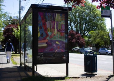 A bright painting is on the side of a bus shelter in Victoria on a sunny day.