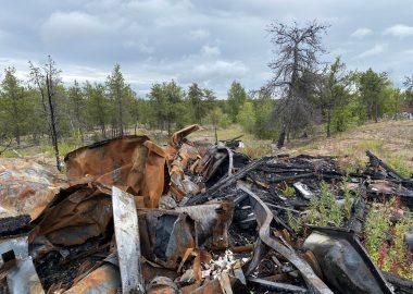 Un amont de ferrailles abandonné en nature, parmi les sapins.