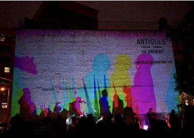 Des projections de couleurs des silouettes de gens dans la rue contre un mur.