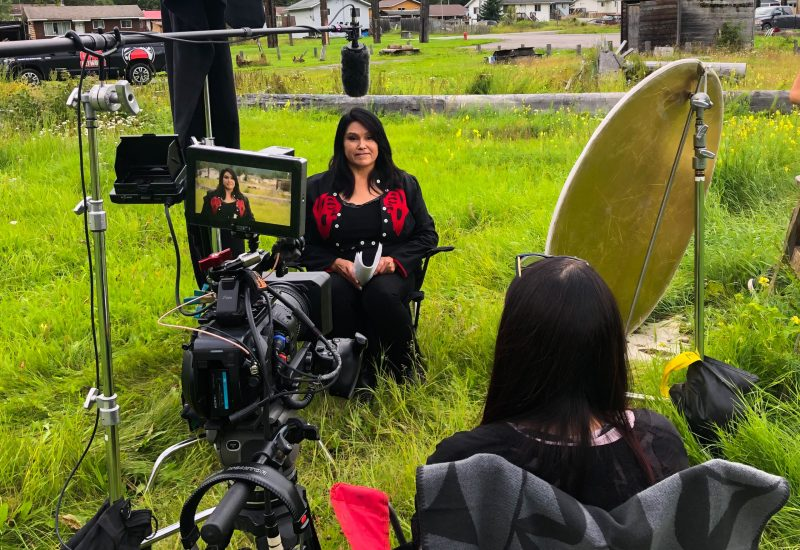 A woman sits in a field on a movie set with camera equipment and other filmmakers surrounding her.