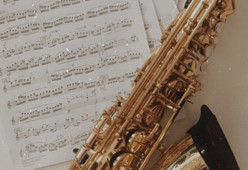 Close up of a saxophone on a table with sheet music underneath it.