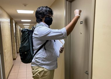 Friendly Neighbour Hotline supports 12,000 seniors in first year. Volunteer pictured knocking on senior's door.
