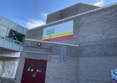 Le devant de l'édifice du CCFM, le drapeau franco-manitobain est affiché sur le mur.