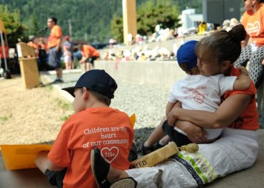 A woman sits with two children at the Indigenous solidarity day in Smithers BC