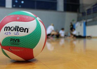 Ballon de volley-ball sur le sol, gymnase, jeunes joueurs en arrière-plan.