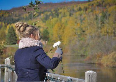 Femme qui a une fleur à la main, devant un lac.