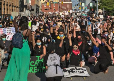 A huge crowd of people with their fists-raised are kneeling in the street in Kitchener during the Black Lives Matter protest. In the foreground signs reading