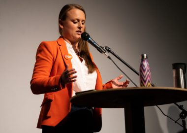 Nelson-Creston MLA Brittny Anderson stands at a podium and a microphone on a stage against a grey and black background
