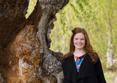 Janine Fisher standing beside a giant tree. On the right of the image, a red-haired and smiling Janine is wearing a black sweater over a colourful top. The tree is on the right of the image - a willow.