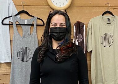 A person in a mask stands in front of printed t-shirt displayed for sale.