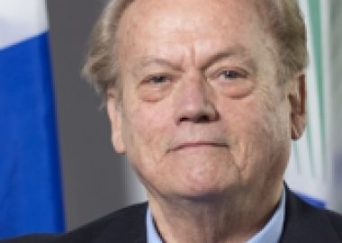 A professional headshot of Jim Gibson, standing in front of a Quebec flag and wearing a navy suit with a blue collared shirt.