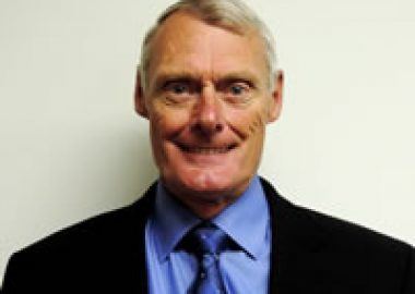 A headshot of Clarendon Mayor John Armstrong, wearing a black suit with a blue shirt.