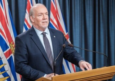 Premier John Horgan stands at a wooden podium during a press conference with BC flags and a blue curtain behind him
