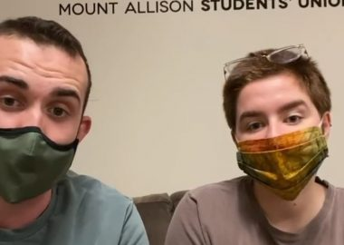 Jon Ferguson and Charlie Burke sit side-by-side on a couch with face masks on.