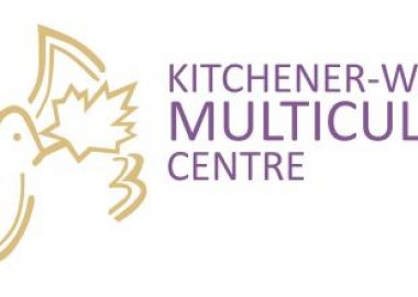 Logo for the KW Multicultural Centre. White background with a basic outline illustration in gold of a dove with a maple leaf in its mouth on the left of the image. taking up 1/3 of the space. In the remaining 2/3ds of the space, in purple text reads