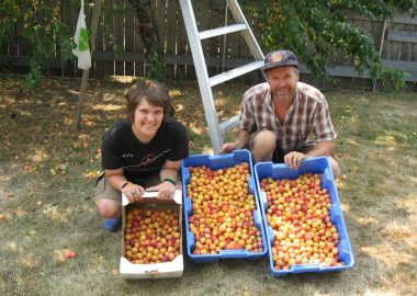 Two people holding buckets of peaches