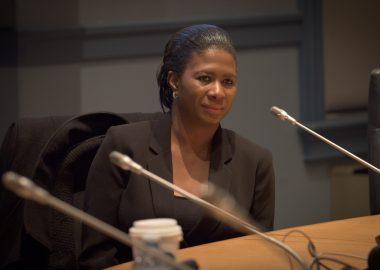 Femme noire assise a une table on voit trois microphones devant elle, la table doit être celle du conseil municipal. La femme en question est Ketcia Peters