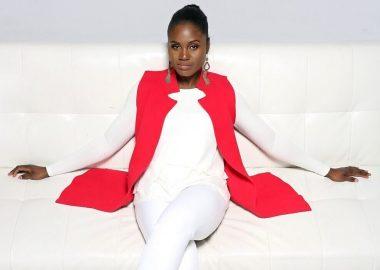 Femme afro descendante portant un pantalon blanc, un corsage blanc et un manteau rouge, assise sur un fauteuil sous forme de sofa. Elle porte des chaussures rouges. Elle a les mains déposées sur le sofa, les jambes croisées.