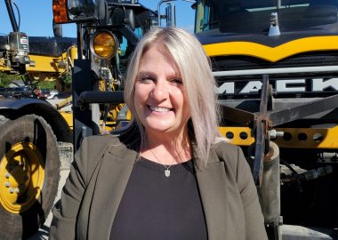 A woman stands in front of a parked dump truck