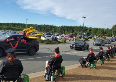 A grad drive-thru parade is seen with a number of vehicles driving by grads sitting in chairs spaced apart on a sunny day