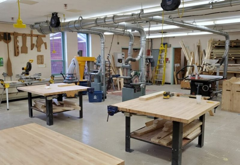 The inside of the tech education shop and classroom at Liverpool Regional High School with four empty wooden worktables and tools in the background