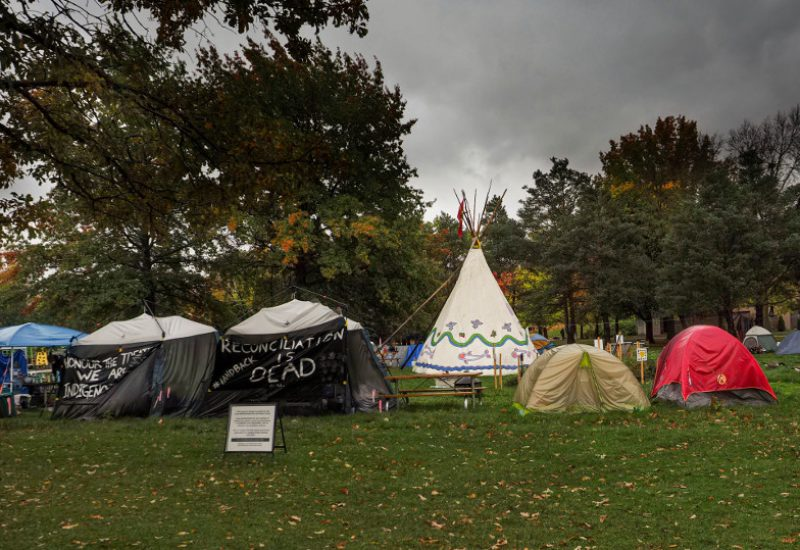 A picture of O:se Kenhionhata:tie/Land back Camp in Victoria Park in Kitchener. Several tents form a circle around a white tee-pee. A black banner hanging on a tent reads