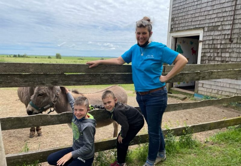 Laura Hunter leans on a fence with her two grandchildren. Behind the fence are two donkeys.