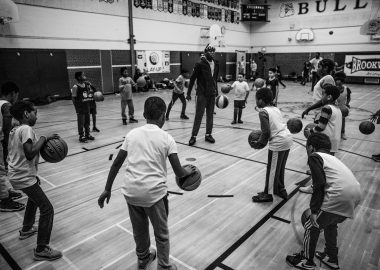 Photo of Lay-Up pre-pandemic, with students dribbling basketballs around their coach in a school gym.