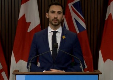 Minister of Education Stephen Lecce stands at a podium at Queen's Park