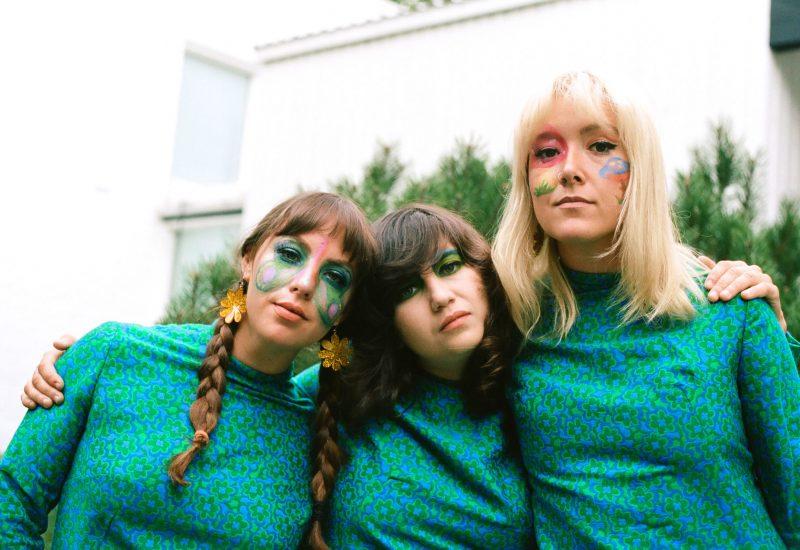 Les Hay Babies, 3 jeunes femmes maquillées habillées en vert devant une maison blanche.