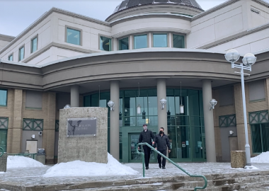 Two people leaving the Prince George courthouse during winter.