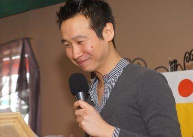 Loc Cory chandail et chemise lignée bleu et blanc; micro à la main tout sourire, yeux fermés devant un lutrin