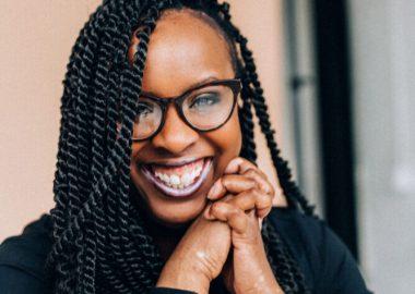 Lydie Dubuisson en noir, tresses africaines et lunettes tout sourire